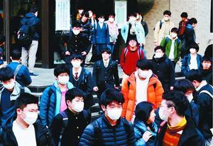 試験を終え、会場を後にするマスク姿の受験生=徳島市の徳島大常三島キャンパス