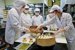 阿波和三盆糖を使った菓子を作る四国大生ら=石井町石井の「岡萬本舗」