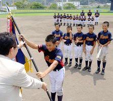 優勝旗を受け取る鷲敷の福永怜央主将=午前11時54分、徳島市のJAバンク徳島スタジアム