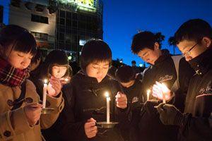 ろうそくをともし祈りをささげる生徒=徳島市の新町橋東公園