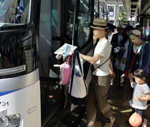 荷物を手に高速バスに乗り込む帰省客や観光客=徳島駅前
