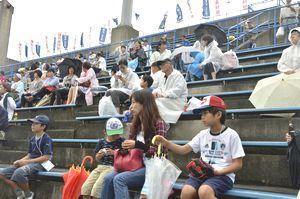 雨の中、好プレーに見入る親子連れら=徳島市のJAバンク徳島スタジアム