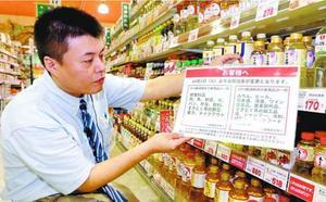 軽減税率対象の品目を示したポスターを取り付ける店員=徳島市のキョーエイタクト店