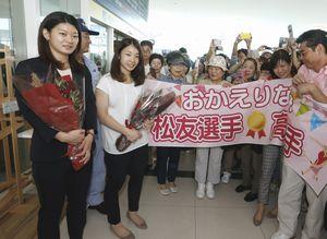 到着ロビーで大勢の県民に出迎えられた松友(手前左から2人目)、高橋(左端)両選手=午前10時20分ごろ、徳島阿波おどり空港