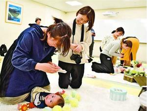 赤ちゃんの写真を撮る参加者ら=徳島市東新町1の阿波銀行本店営業部
