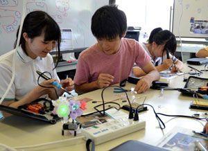 高専生(中)に教わりながら、イルミネーション回路を作る中学生=阿南市の阿南高専