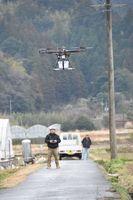 荷物を搭載して飛行する小型無人機ドローン=24日、那賀町和食郷