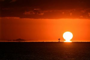 水平線の上に姿を現した「だるま朝日」。左に浮いて見えるのは和歌山県の沿岸部=午前6時51分、徳島市のマリンピア沖洲から