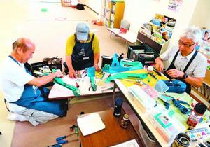 仲間と共におもちゃを修理する大西さん(右)=吉野川市の鴨島児童館