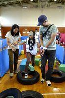 障害物が並べられた道を協力し合って進む参加者=徳島市B&G海洋センター体育館