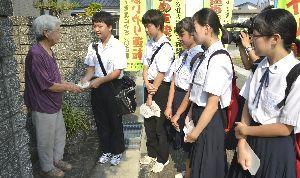 手書きのメッセージカードを添えて啓発チラシを手渡す北島中の生徒=北島町鯛浜