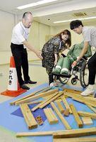 教材を使い、車いす利用者の適切な避難介助の方法を学ぶ学生=徳島市の徳島文理大