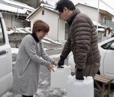 市職員(右)からポリタンクに入った水を受け取る住民=三好市池田町馬路