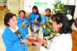 医師(右)にケーキを贈る地域医療を守る会のメンバー=海陽町の海南病院