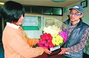 預かり事業の職員にバラの花束を渡す岡松社長(右)=海陽町奥浦老人福祉センター