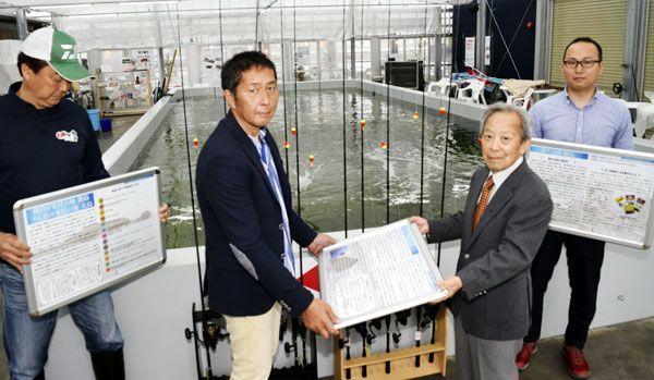 森永社長(左から2人目)にパネルを手渡す阿波釣法振興会の高橋事務局長=徳島市東沖洲2の「徳島新鮮なっとく市」