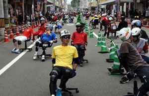 事務用椅子で商店街を力走する参加者=鳴門市の大道商店街