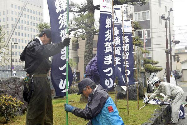 鷲の門広場周辺に祭りの開催を知らせるのぼりを設置する実行委スタッフら=徳島市徳島町城内