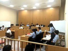被告人役の女性(左)に質問する城東高生=高松地裁(日弁連提供)