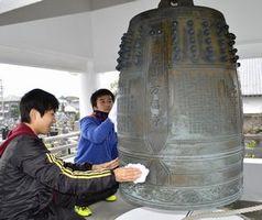 釣り鐘の汚れを拭く参加者=徳島市吉野本町5の万福寺