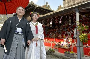 ひな人形で彩られた「坂本おひな街道」を歩く柴田洸二郎さん(左)と宇希美さん=勝浦町坂本