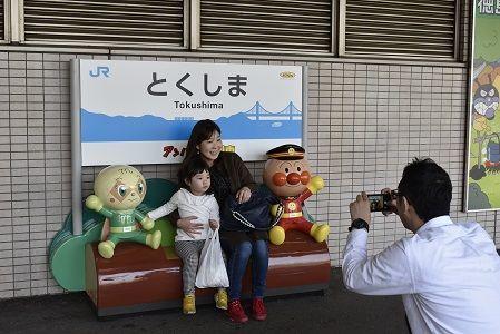 アンパンマンベンチで記念撮影する家族連れ=徳島駅