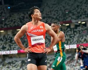 男子100メートル予選 10秒15の3組4着でゴールし、電光掲示板を見つめる山県亮太(手前)=国立競技場