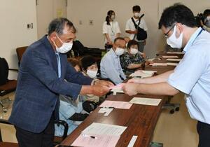 広島市役所で被爆者健康手帳を受け取る「黒い雨」訴訟原告団長の高野正明さん(左)=2日午後