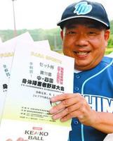 協賛金を活用して製作した中四国身体障害者野球大会のパンフレットを持つ西上代表
