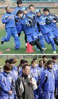 【上】キャンプ初日から精力的に走り込む徳島の選手たち=高知県春野総合運動公園球技場【下】歓迎セレモニーであいさつする小林監督(中央)