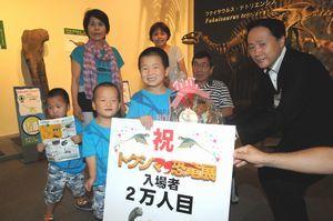 来場2万人目の記念品を受け取る耕平ちゃん(手前中央)=徳島市の県立博物館
