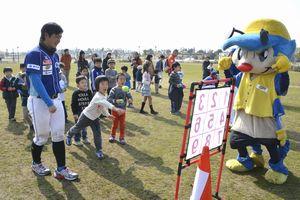 選手のアドバイスで的に向かってボールを投げる子どもら=松茂町の月見ケ丘海浜公園