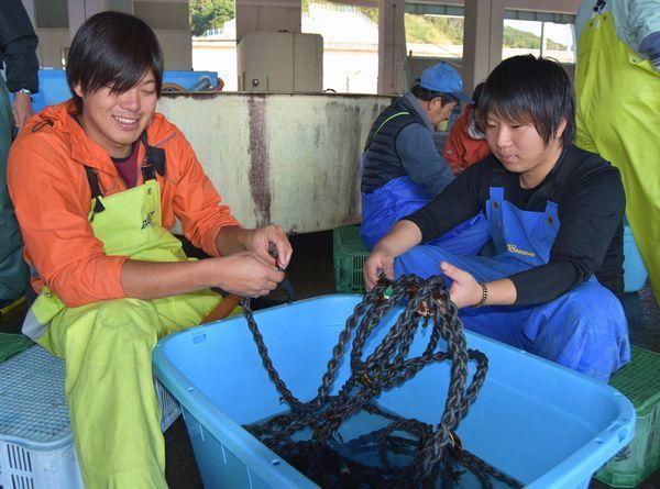 養殖ワカメの種苗をロープに差し込む海藻部の漁師たち=美波町港町の西由岐漁協