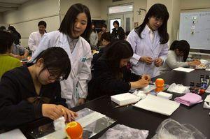 ミカンの皮を使った実験に取り組む中高生ら=徳島大常三島キャンパス