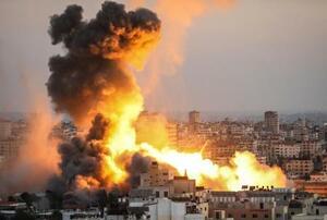 14日、パレスチナ自治区ガザで、イスラエル軍による空爆後に煙が上がる建物(ゲッティ=共同)