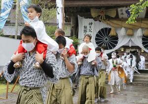 「湯登神事」で、父親に肩車され熊野本宮大社を出発する稚児たち=13日午前、和歌山県田辺市