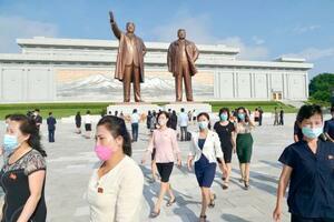 万寿台の丘に立つ故金日成主席(左)と故金正日総書記の銅像へ献花に訪れた市民ら=19日、平壌(共同)