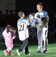 日本ハムのファン感謝イベントで、家族から花束を受け取る武田久投手=札幌ドーム