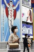 大阪・ミナミの戎橋を歩くマスク姿の女性=13日、大阪市