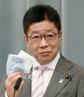 記者会見で、陽明学者山田方谷のキャラクターがデザインされたマスクを手にする加藤官房長官=24日午前、首相官邸