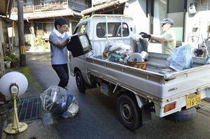 被害を受けた家屋のゴミを運び出す町職員=午前9時49分、海陽町鞆浦