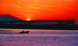 建設中の高架道路が夕焼けに浮かぶ今切川河口。漁を終えた船が次々と帰ってくる=松茂町長原