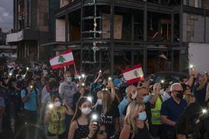 9日、レバノン・ベイルートで懐中電灯を手に大規模爆発の犠牲者を追悼する人々(AP=共同)