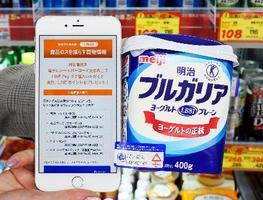電子タグ(左下)を貼り付けた商品と、ポイント還元を知らせるスマートフォンのデモ画面=12日、東京都江東区の「ココカラファイン清澄白河店」