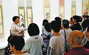美人画の着物の模様や帯について解説する内山さん=徳島市の県立近代美術館