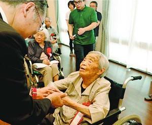 飯泉知事(左)と握手する古川さん=阿南市宝田町の琴江荘
