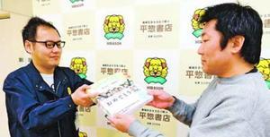 八百原店長(左)から放課後児童クラブに届ける絵本を受け取る岸上さん=徳島市の平惣徳島店