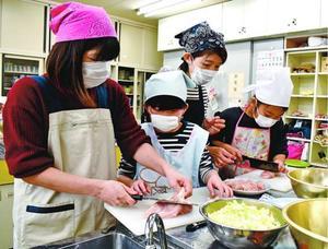 協力し合って料理を作る親子=徳島市国府町日開の南井上コミュニティーセンター