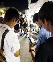スマホの画面に集中しゲームを楽しむ高校生=徳島市の藍場浜公園
