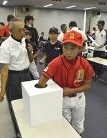 こども野球のつどいの組み合わせ抽選で、くじを引く選手ら=徳島市の新聞放送会館